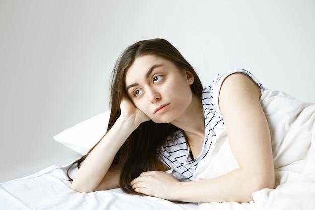 縞模様のパジャマ姿の美しい若いブルネットのヨーロッパ人女性は、ベッドに横たわっている間、孤独を感じ、思慮深い表情で横向きに退屈して死ぬ 無料写真