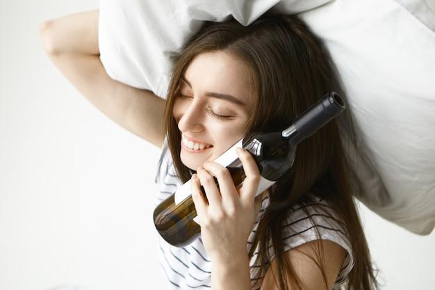 Bella giovane donna bruna avendo postumi di una sbornia che tiene cuscino bianco sulla sua testa e una bottiglia di alcol sulla sua guancia Foto Gratuite