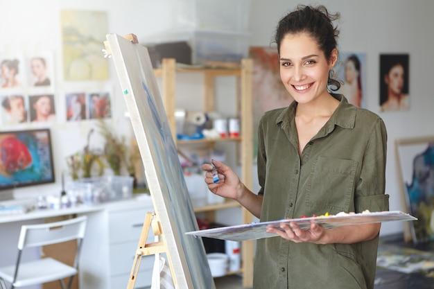 La bella giovane pittrice si è vestita casualmente mentre lavorava nel suo laboratorio, in piedi vicino a cavalletto, creando un'immagine con acquerelli colorati Foto Gratuite