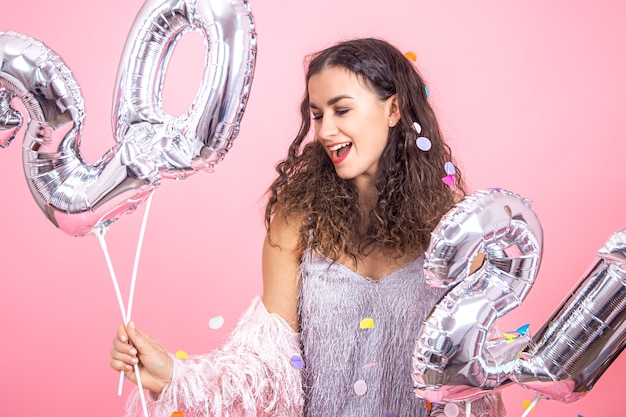 Beautiful young brunette girl with curly hair and festive clothes posing on a pink studio background with confetti and holding in her hand silver balloons for the new year concept Free Photo