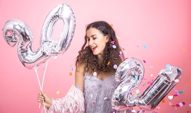 색종이와 핑크 스튜디오 배경에 포즈와 새 해 개념에 대 한 그녀의 손은 풍선에 들고 곱슬 머리를 가진 아름 다운 젊은 갈색 머리 소녀 무료 사진