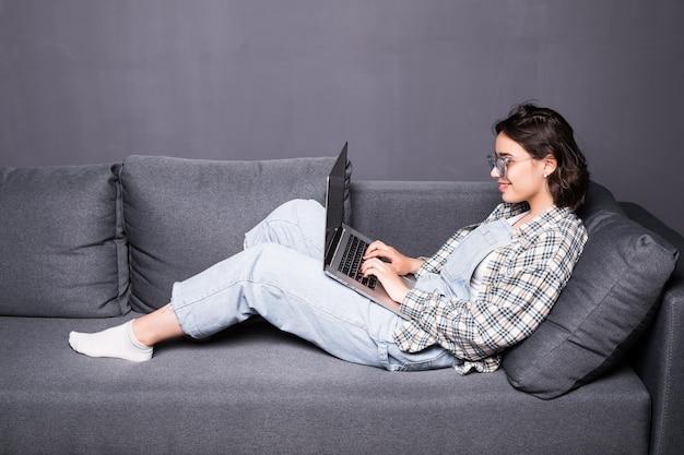 Bella giovane donna bruna a casa seduta sul divano o divano utilizzando il suo computer portatile e sorridente Foto Gratuite