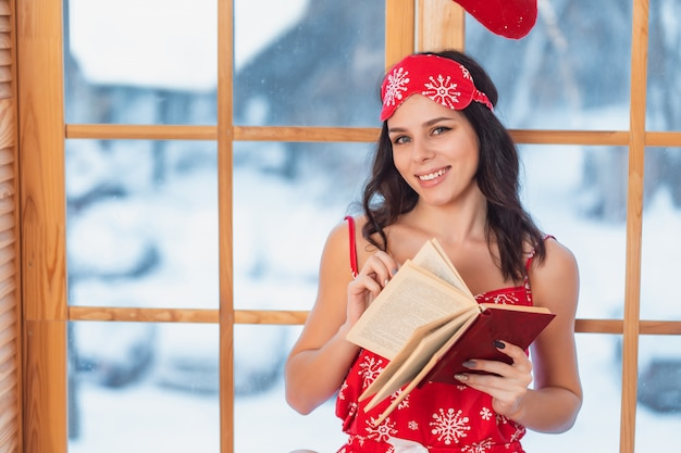 Beautiful young brunette woman wearing red pajamas and reading by the window Free Photo