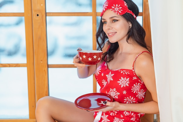 Beautiful young brunette woman wearing red pajamas sitting home by the window Free Photo