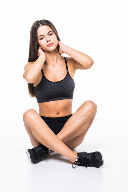 Beautiful young brunette woman wearing sports clothes sitting on the floor isolated on white Free Photo