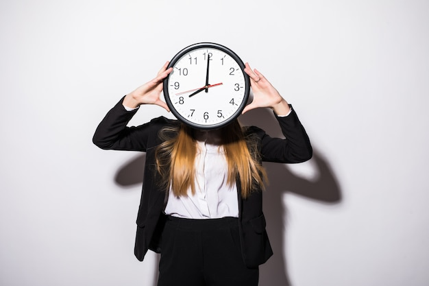 Beautiful young business woman holding clock in front of face on white Free Photo