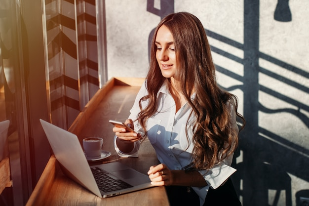 Beautiful young business woman in white blouse using laptop and smartphone, drinks coffee at a table in a cafe Premium Photo