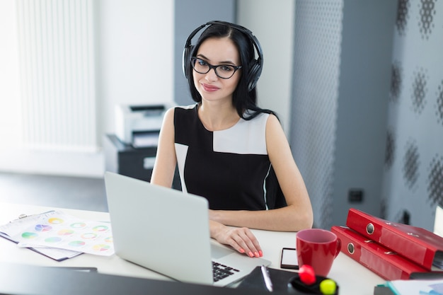 Beautiful young businesswoman in black dress, headphones and glasses sit at the table and work on laptop Premium Photo