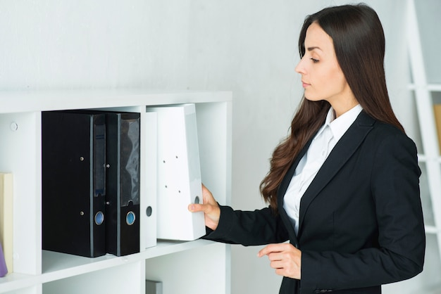 Beautiful young businesswoman removing white folder from the shelf in the office Free Photo