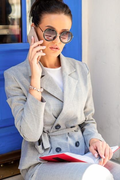 거리에 블루 문 앞 계단에 선글라스를 착용 스마트 폰으로 아름 다운 젊은 백인 비즈니스 여자 회담 프리미엄 사진