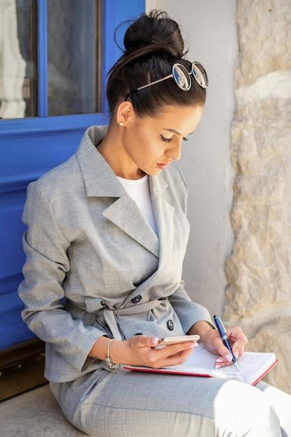 문 계단에 앉아있는 동안 메모를 복용하는 아름 다운 젊은 백인 사업가 프리미엄 사진