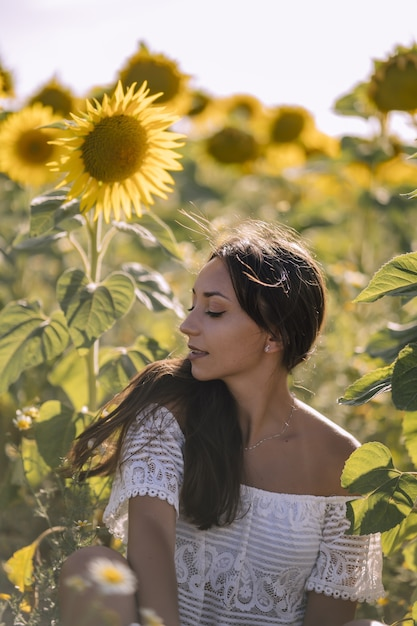 Beautiful young caucasian female posing in a field of sunflowers Free Photo