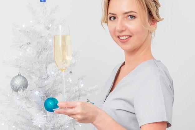 Красивая молодая кавказская улыбающаяся женщина-врач в защитных перчатках с бокалом шампанского стоит возле елки Premium Фотографии