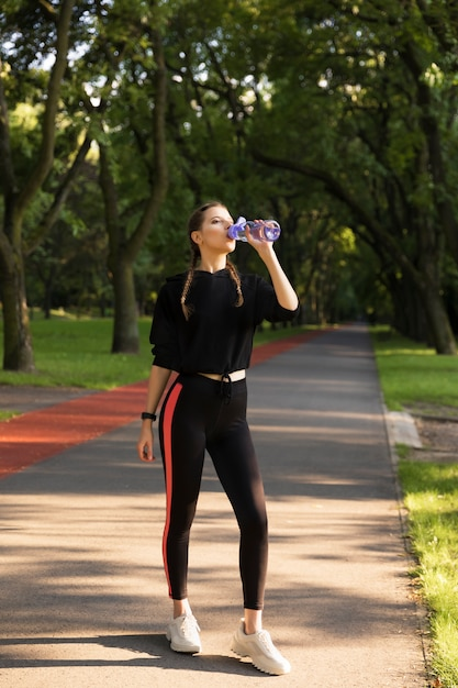 Beautiful young caucasian woman in fitness wear working out in a park. Premium Photo