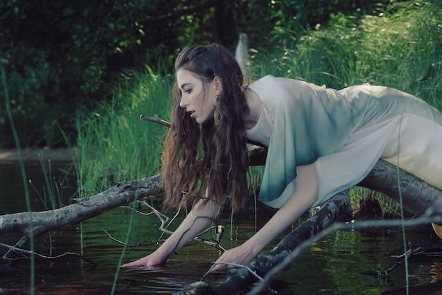 Красивая молодая кавказская женщина, опираясь на ветку дерева над рекой, пытается добраться до воды. Premium Фотографии