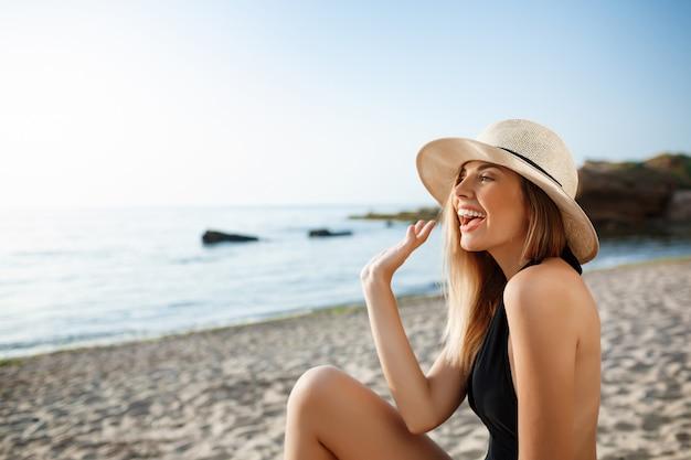 朝のビーチでかかっている帽子の美しい陽気な少女 無料写真