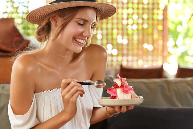 Beautiful young cheerful woman with bare shoulders, eats delicious piece of cake, comes on friend`s birthday party at cafe, dressed in summer clothing, has delighted look. relaxed female with dessert Free Photo