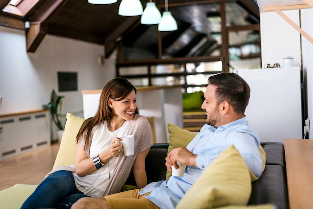 Beautiful young couple drink coffee while sitting on a sofa, looking each other Premium Photo
