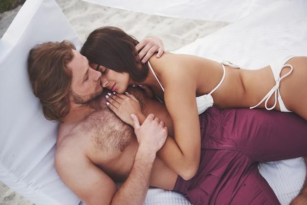 砂の笑顔と抱擁に対してビーチで水着で美しい若いカップル。 無料写真