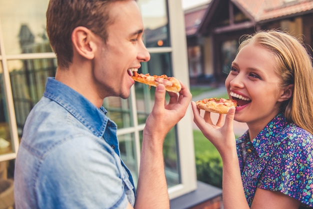 Beautiful young couple is eating pizza. Premium Photo