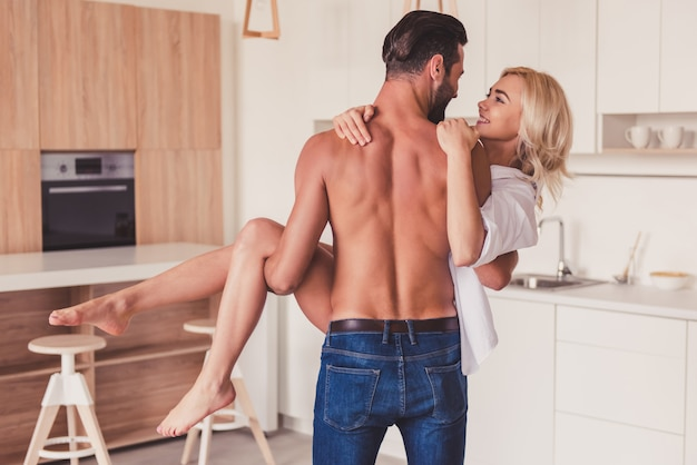 Beautiful young couple is having fun in kitchen at home. Premium Photo