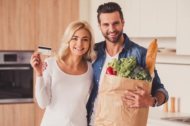 Beautiful young couple is holding a paper bag. Premium Photo