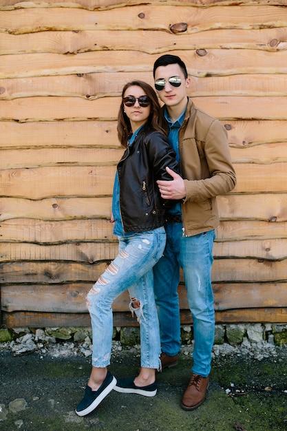 Belle giovani coppie che posano sopra la parete di legno Foto Gratuite