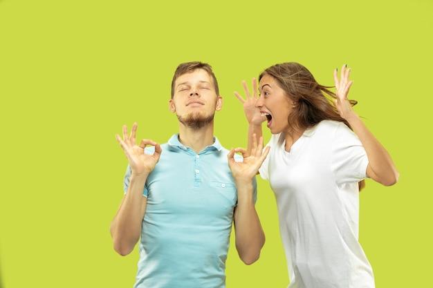 孤立した美しい若いカップルの半身像。男性は女性が叫んでいる間、目を閉じて落ち着きを保とうとしています。顔の表情、人間の感情の概念。 無料写真