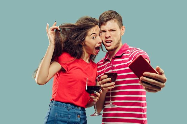 孤立した美しい若いカップルの半身像。笑顔の女性と男性がワインとグラスを持って自分撮りをしています。表情、夏、週末のコンセプト。 無料写真