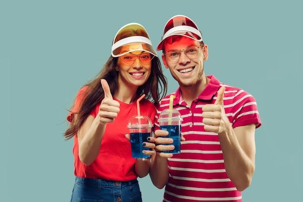 孤立した美しい若いカップルの半身像。飲み物と帽子とサングラスで笑顔の女性と男性。表情、夏、週末のコンセプト。トレンディな色。 無料写真