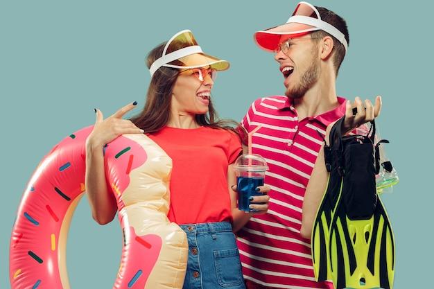 孤立した美しい若いカップルの半身像。水泳用品と帽子とサングラスで笑顔の女性と男性。表情、夏、週末のコンセプト。 無料写真
