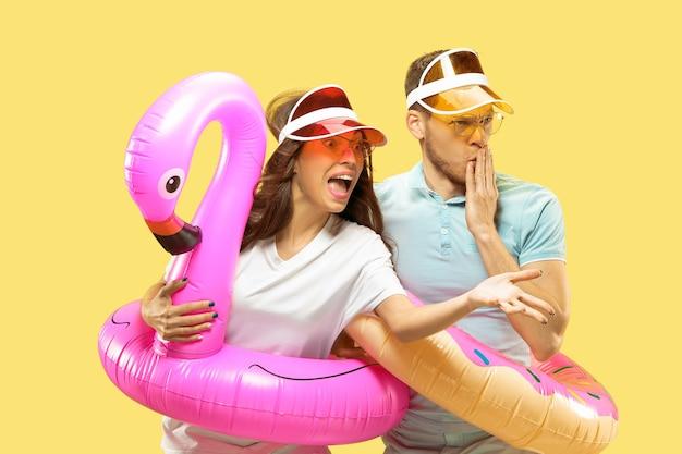 孤立した美しい若いカップルの半身像。浮き輪で立っている帽子とサングラスの女性と男性。表情、夏、週末のコンセプト。 無料写真