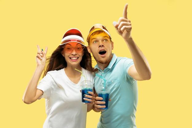Поясной портрет красивой молодой пары изолирован. женщина и мужчина, стоя с напитками в красочных шапках. выражение лица, лето, концепция выходных. модные цвета. Бесплатные Фотографии