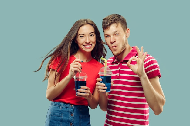 孤立した美しい若いカップルの半身像。飲み物を持って立っている女性と男性が笑顔で署名ok。表情、夏、週末のコンセプト。トレンディな色。 無料写真