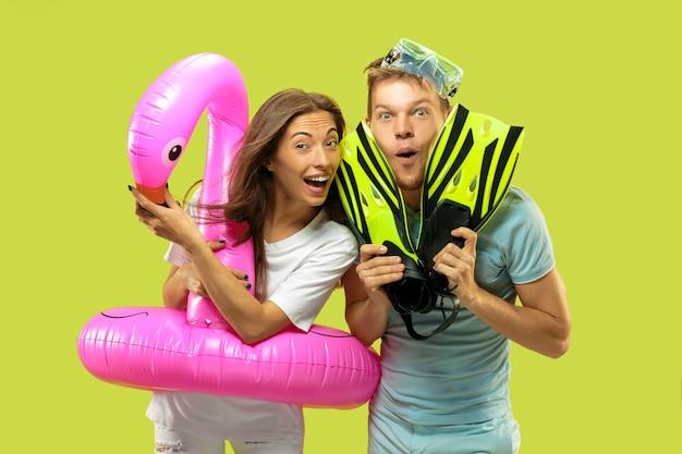 美しい若いカップルの半身像。フラミンゴと足ひれとしてピンクの浮き輪で立っている女性と男性。表情、夏、週末のコンセプト。 無料写真