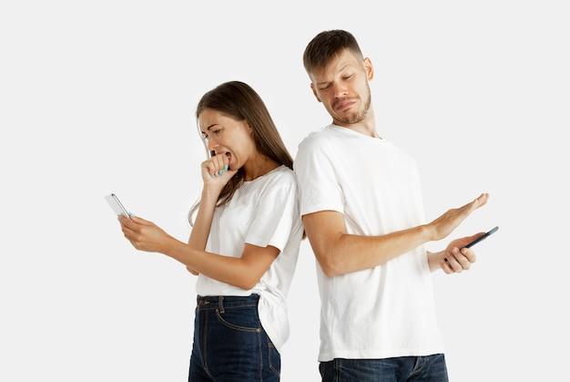 Ritratto della bella giovane coppia isolato. espressione facciale, emozioni umane. uomo e donna che tengono smartphone e sembrano spaventati dal suo schermo. Foto Gratuite