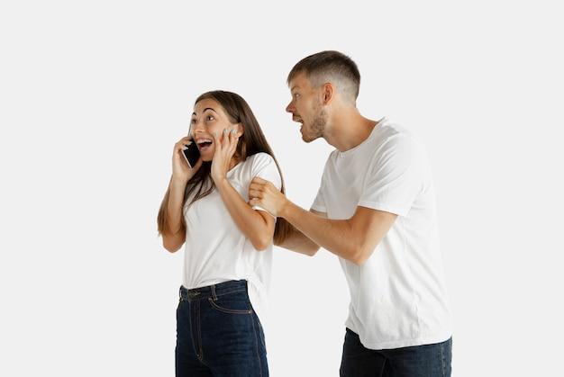Ritratto della bella giovane coppia isolato. espressione facciale, emozioni umane. donna che parla al telefono, l'uomo vuole prestare la sua attenzione su se stesso. Foto Gratuite