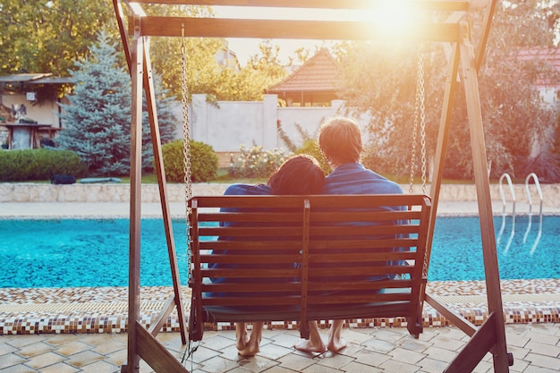 Beautiful young couple sitting at the bench by the pool Free Photo