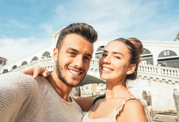 Beautiful young couple taking a selfie enjoying the time on their trip to venice Premium Photo