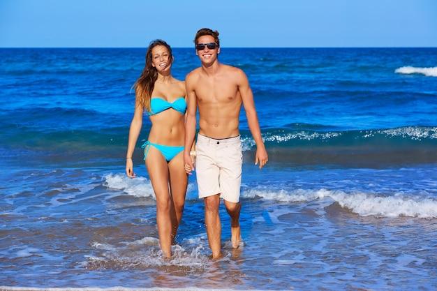Beautiful young couple walking in the beach Premium Photo