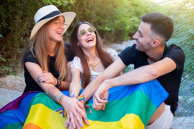 Lgbtコミュニティの平等な権利、虹色の旗を優しく抱き締めるレズビアンの少年と美しい若いカップル Premium写真