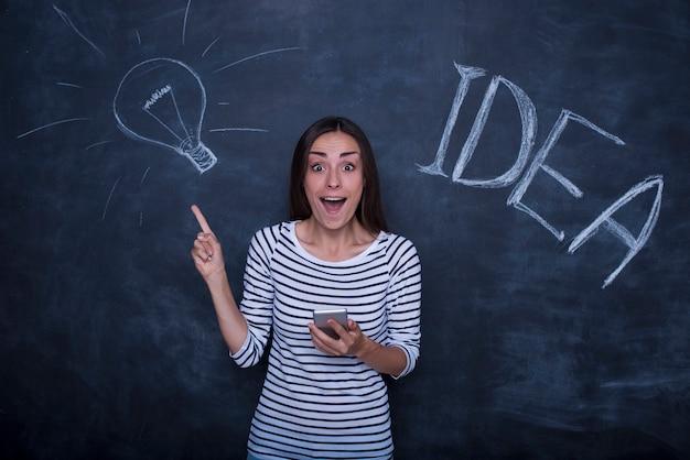 Красивая молодая возбужденная женщина позирует на фоне классной доски с изображением идеи лампы. Premium Фотографии