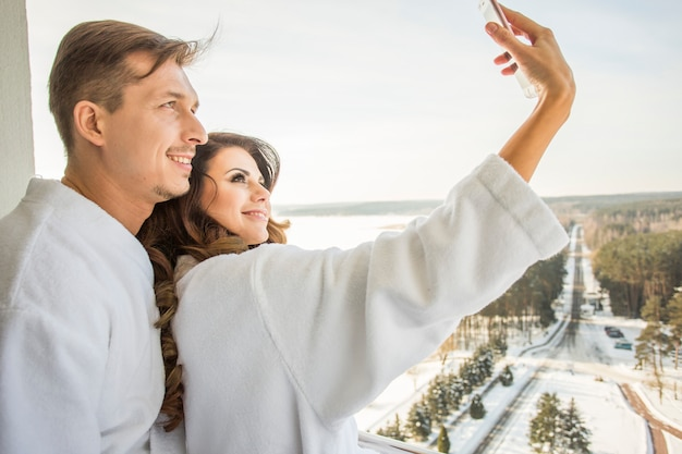 Beautiful young family couple in white bathrobes have fun take selfie on terrace Premium Photo