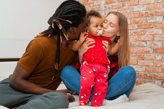 Beautiful young family with little daughter at home Premium Photo