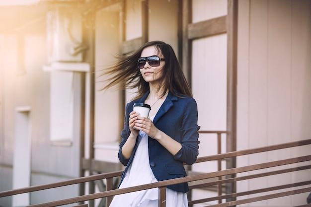 美しい若いファッションの女の子は、持ち帰り用のコーヒーを手にカフェから来ています Premium写真
