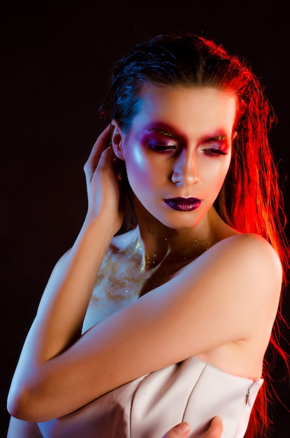 Beautiful young fashionable girl with art make-up in color light Premium Photo