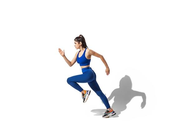 Bella giovane atleta femminile che pratica su sfondo bianco studio, ritratto con le ombre. modello dalla vestibilità sportiva in movimento e in azione. Foto Gratuite