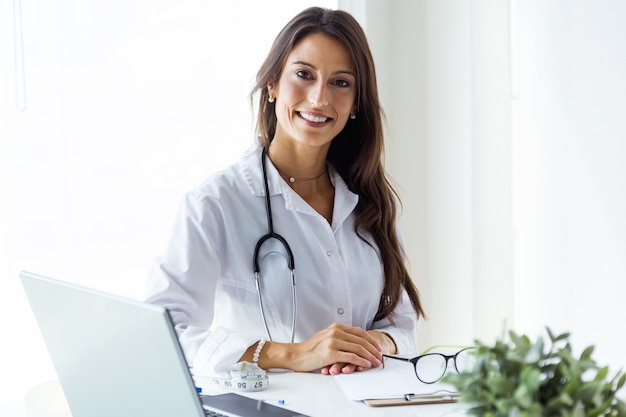 Beautiful young female doctor looking at camera in the office. Free Photo
