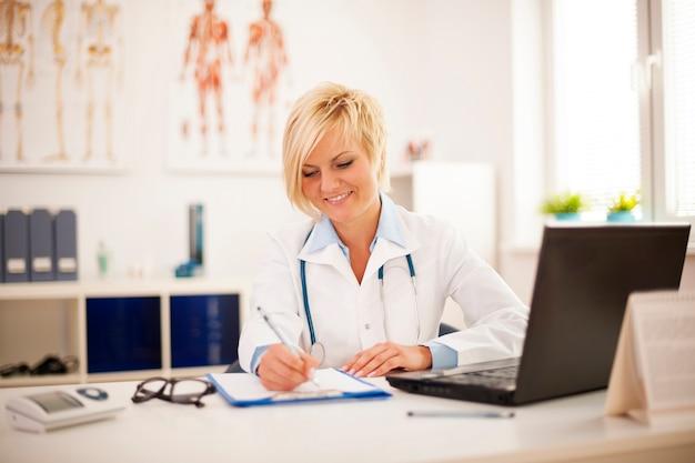 Bello giovane medico femminile che lavora nel suo ufficio Foto Gratuite