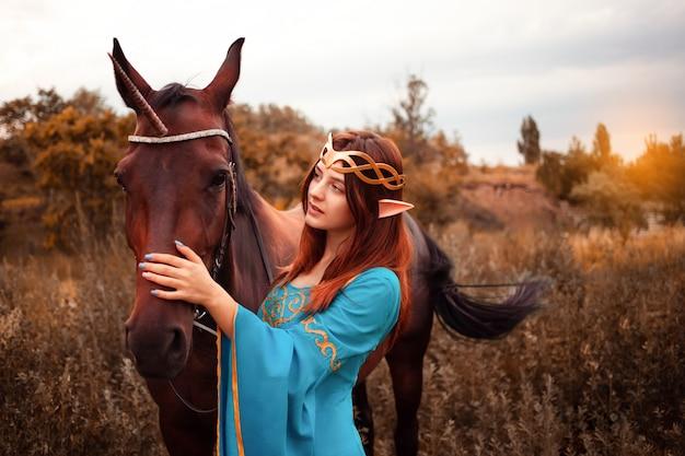 森の森のニンフで休んでいる彼女の馬をかわいがる長い暗いウェーブのかかった髪を持つ美しい若い女性のエルフ彼女の馬の世話をするペットの愛の動物の調和思いやりのある所有者優しい生き物の神話 Premium写真